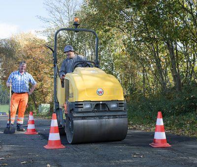 Mitarbeiter des Bauhofes flicken mit einer Maschine die Straße